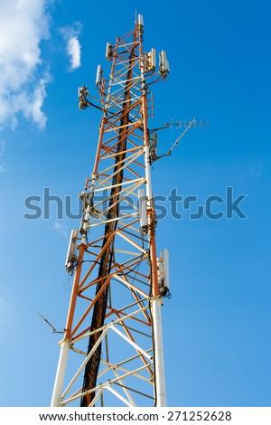 High antenna mast isolated on blue sky background - stock photo