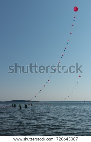 High balloons, pennants and volunteers mark the lanes for a summer swim and kayak race, with copy space