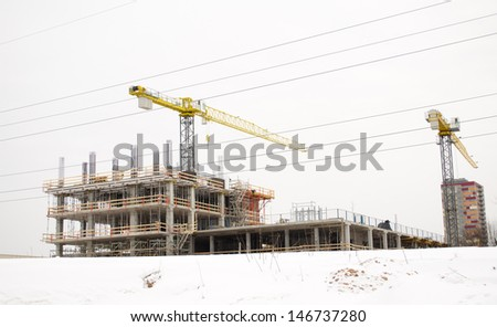 high building under construction and cranes on background of cloudy sky and winter snow.  - stock photo