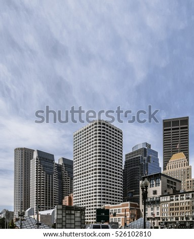 High buildings of financial district of modern city in front of blue sky with clouds, Boston MA