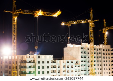 high buildings under construction with cranes at night in motion - stock photo