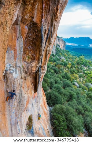 High colorful rock and two climbers ascending green garden and mountains dramatic sky on background