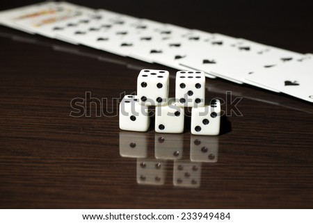 High contrast black and white image of gaming dice and a row of playing cards.