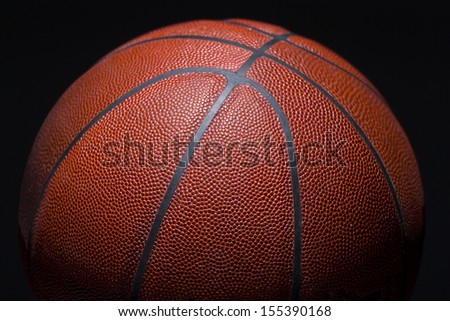high contrast closeup of basketball on black background - stock photo