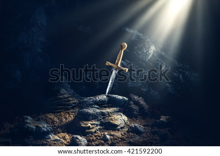 High contrast image of Excalibur, sword in the stone with light rays and dust specs in a dark cave - stock photo
