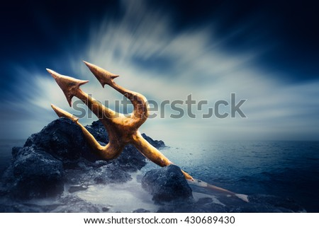 High contrast image of Poseidon's trident resting on some rocks by the sea - stock photo