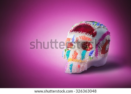 "High contrast image of sugar skull used for ""dia de los muertos"" celebration in a pink background - stock photo"
