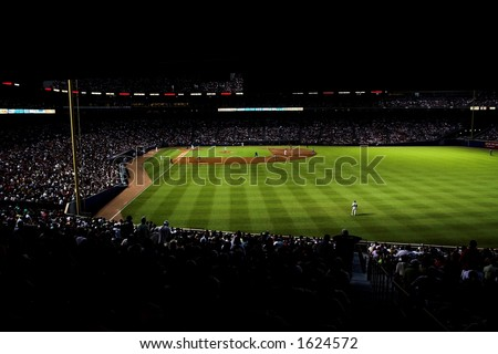 high contrast image of Turner Field at night; the stadium is highlighted in green, with crowd very dark - stock photo