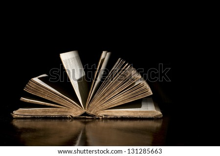 High contrast light on an open antique bible with black background and good copy space