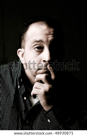 High contrast portrait of a middle aged man with a contemplative look on his face.  He could be worried or anxious about something on his mind. - stock photo