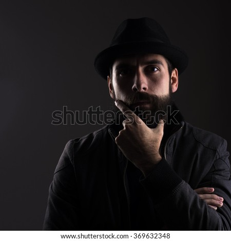 High contrast portrait of serious bearded man wearing black hat thinking looking at camera over black background.  - stock photo