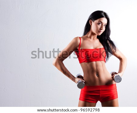 high contrast studio portrait of a beautiful sporty muscular woman working out with two dumbbells, copyspace to the left