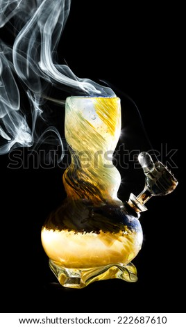 high contrast studio shoot of a bong with simulated marijuana smoke on a black background - stock photo