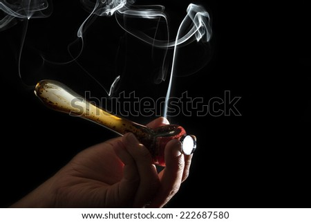 high contrast studio shoot of a pipe with simulated marijuana smoke on a dark background - stock photo