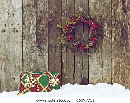 High contrast vintage image of a home made christmas wreath with natural decorations hanging on a rustic wooden wall and two gifts in the snow. - stock photo