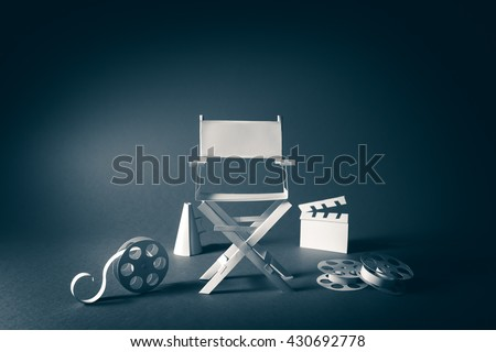 high contrast vintage image of Director chair and several movie items made from paper on a wood surface - stock photo
