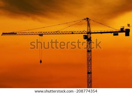 high crane silhouette on cloudy evening lighting - stock photo