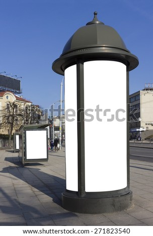 High curbstone with billboard advertizing near a stop of public city transport. Sunny spring day. With patches isolated empty areas