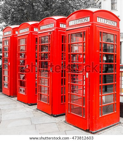 High dynamic range HDR Red telephone box in London over desaturated black and white background