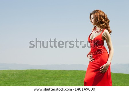 high end fashion shot of sexy red hair girl wearing red dress in complementary green grass field in sunny day - stock photo