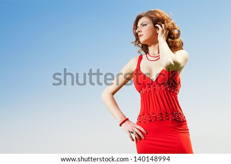 high end fashion shot of sexy red hair girl wearing red dress with vibrant clear blue sky in background in sunny day - stock photo