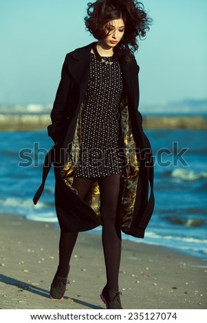 High fashion concept. Emotive portrait of beautiful brunette with long curly hair wearing black coat and little black dress & walking along beach. Windy weather. Italian luxurious style. Outdoor shot - stock photo