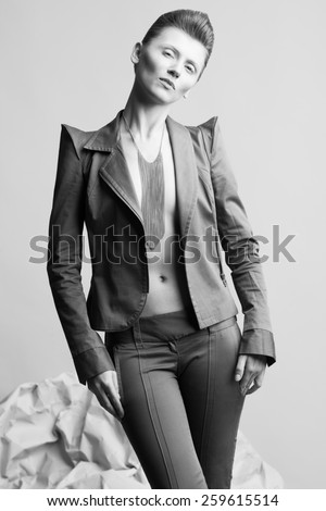 High fashion concept. Portrait of androgynous model with short hair wearing long silver necklace posing over gray background. Pale skin, natural make-up. David Bowie style. Studio shot - stock photo