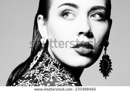 High fashion concept. Portrait of glamorous young model with long wet hair, luxurious earrings and perfect make-up posing over gray background. Deep shadows. Vogue style. Close up. Studio shot - stock photo