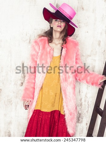 High fashion girl posing near the stair in studio in hat and pink fur coat  - stock photo
