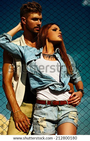 High fashion look.beautiful couple sexy stylish blond young woman model with bright makeup with perfect sunbathed skin and handsome muscled man in vogue style in jeans outdoors behind blue sky - stock photo