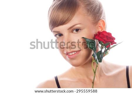 High fashion look. Close-up portrait of a young girl with a glamorous nude makeup and clean skin. The girl holds a rose flower. Isolated on white background.