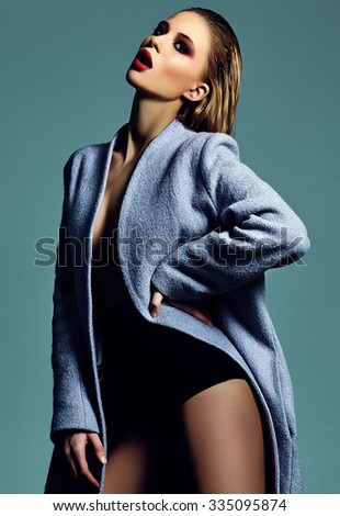 High fashion look.glamor beautiful sexy hot stylish young blond woman model with bright makeup in overcoat in studio - stock photo