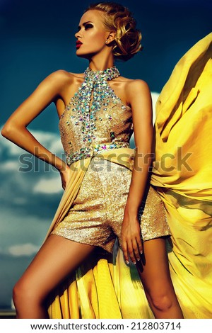 High fashion look.glamor beautiful sexy stylish blond young woman model with bright makeup and red lips with perfect sunbathed clean skin in vogue style in evening yellow dress behind blue sky - stock photo