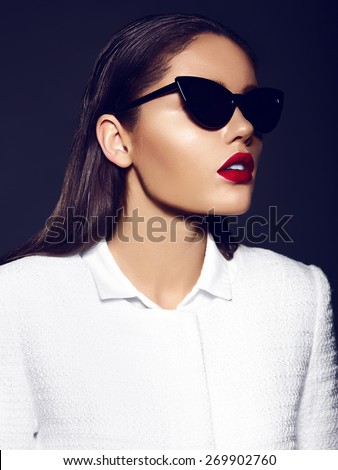 High fashion look.glamor closeup portrait of beautiful sexy stylish brunette young woman model with bright makeup with red lips in white coat jacket in sunglasses - stock photo