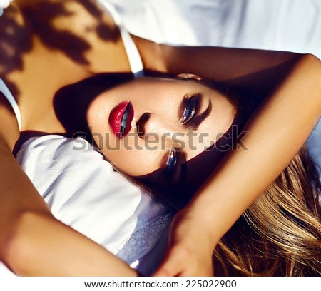High fashion look.glamor closeup portrait of beautiful sexy stylish  young woman model lying on white bed with bright makeup, with red lips,  with perfect clean skin in white lingerie - stock photo