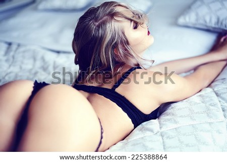 High fashion look.glamor closeup portrait of beautiful sexy stylish  young woman model lying on white bed with bright makeup, with red lips,  with perfect clean skin in black lingerie on bed - stock photo