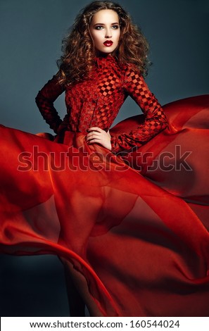 High fashion look.glamor portrait of beautiful sexy stylish brunette Caucasian young woman model with bright makeup, with healthy curly hair in bright red flying dress in studio - stock photo