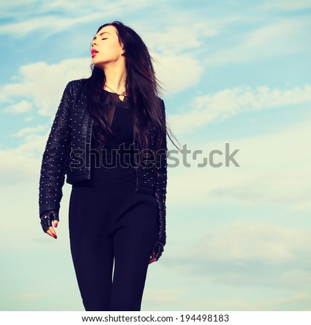 High fashion look. Glamor portrait of beautiful sexy stylish Caucasian young woman model in black cloth. Young woman outdoors fashion portrait. Soft sunset light. Instagram style square pic