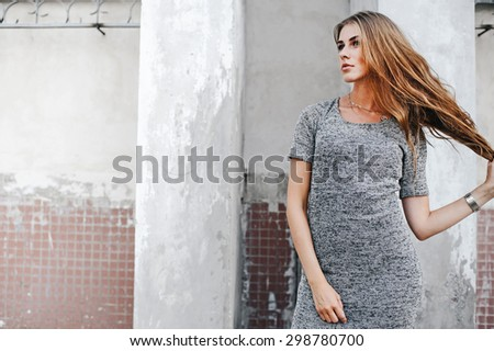 High fashion look.glamor portrait of beautiful sexy stylish Caucasian young woman model in dress against wall - stock photo