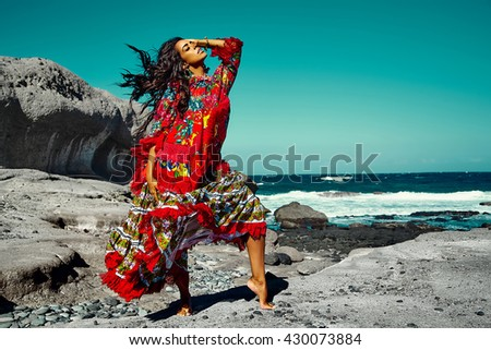High fashion look.glamor sexy Caucasian model girl in red colorful red dress posing behind blue beach ocean water in vogue style
