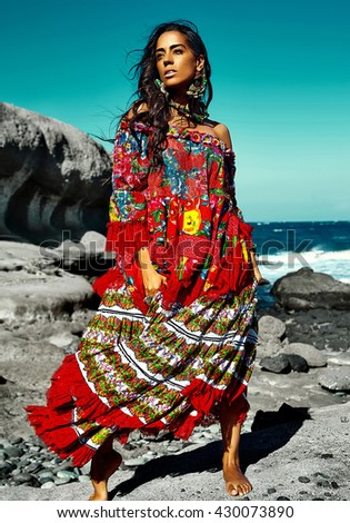 High fashion look.glamor sexy Caucasian model girl in red colorful red dress posing behind blue beach ocean water in vogue style - stock photo