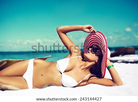 High fashion look.glamor sexy sunbathed model girl in white lingerie bikini in colorful sunhat behind blue beach ocean water