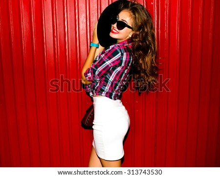 High fashion look.glamor stylish beautiful young woman model with red lips in bright colorful hipster cloth,happy girl,denim jacket,smiling,cool accessories,purse,hat,sunglasses,amazed,vintage style - stock photo