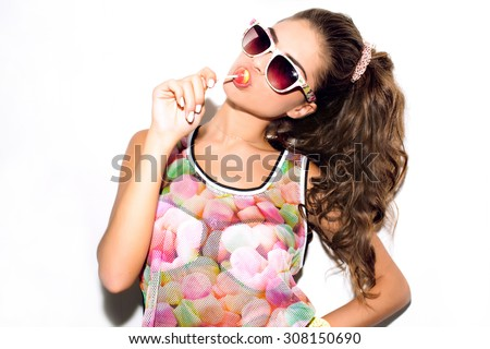 High fashion look.Glamor stylish beautiful young woman model with red lips in summer bright colorful hipster cloth,sunglasses,eat sweats.studio,eat lolly pop,isolated on white,candy woman,marshmallows - stock photo