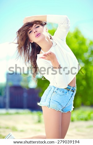 High fashion look.glamor stylish sexy smiling beautiful sensual young woman model in summer bright hipster cloth in jeans shorts in the street giving kiss - stock photo