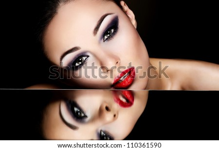 High fashion look.glamour fashion portrait of beautiful sexy brunette girl female model with bright makeup and red lips and her reflection in mirror table on dark with perfect skin