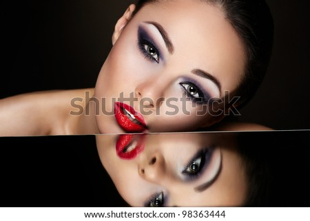 High fashion look.glamour fashion portrait of beautiful sexy brunette girl with bright makeup and red lips and her reflection in mirror table on dark - stock photo