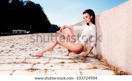 High fashion look.glamour portrait of beautiful sexy brunette female model girl in white lingerie outdoors .blue sky.sitting near sea - stock photo