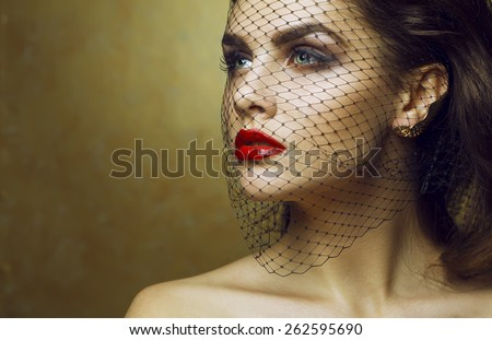 High fashion look. Portrait of a fashionable model with sexy red lips, beautiful naked shoulders, perfect skin and through black veil. Close up. Studio shot. Copy space - stock photo