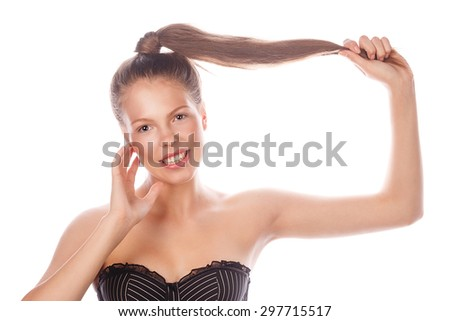 High fashion look. Portrait of a teen girl with Nude makeup, hair and clean skin. The girl smiles and holds her hair. The concept of a young beauty.